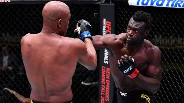 Uriah Hall, right, punches Anderson Silva in a